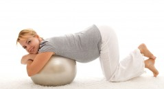 Beautiful woman exercising with large ball