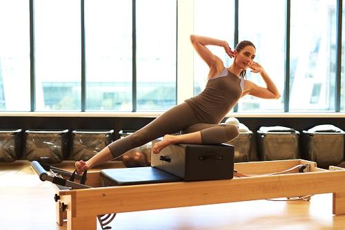 brunette woman practicing pilates in studio P5FWVYD - Cómo ser profesor de pilates en la actualidad