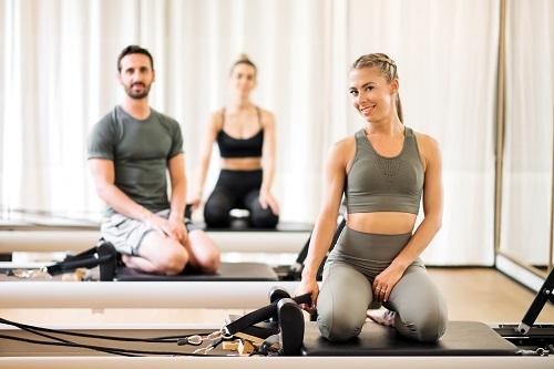 three athletes posing on reformer beds at gym 2FHXLCW - Cómo ser profesor de pilates en la actualidad