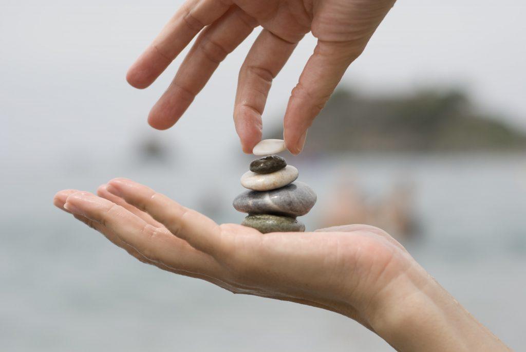 putting last pebble pile stones 1024x685 - Wellness como complemento al Pilates